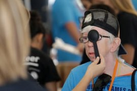 "An athlete gets a free eye exam in ""olympic town"" at the Indiana Special Olympics."